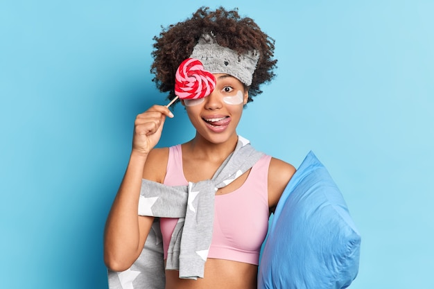 Pretty curly haired woman covers eye with sweet candy licks lips dressed in casual clothes applies collagen patches before sleeping holds pillow isolated on blue wall