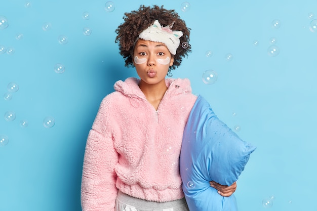 Pretty curly haired woman keeps lips folded wants to kiss you undergoes beauty procedures after awakening dressed in nightwear holds pilloe surrounded by soap bubbles isolated over blue wall