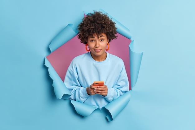 かなり縮れ毛の女性がソーシャルネットワークでテキストメッセージに携帯電話を使用して携帯電話を保持