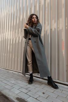 빈티지 패션 긴 코트와 부츠를 신고 꽤 곱슬곱슬한 모델 여성이 거리의 금속 벽 근처에 서 있습니다. 어반 캐주얼 모던 스타일과 여성미