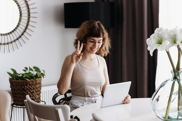 Pretty curly smiling young girl talking by phone sitting at the table at home. video chatting with friends