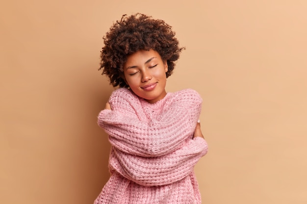 Pretty curly woman embraces herself and closes eyes feels comfort in soft warm knitted sweater enjoys home tenderness tilts head poses against beige wall