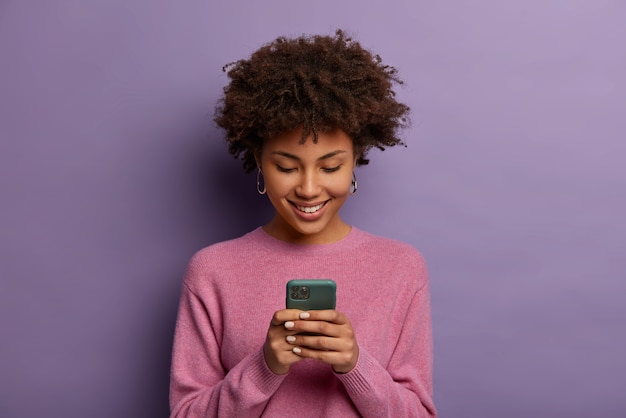 Pretty curly woman holds modern mobile phone, types messages on smartphone device, enjoys online communication, downloads special app for chatting, smiles tenderly, isolated on purple  wall