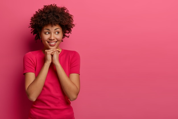 Pretty curly woman keeps hands under chin, chuckles positively and looks on right side, fascinated by something appealing, wears casual t-shirt, isolated on pink wall, free space aside