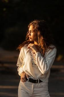 세련된 니트 스웨터를 입은 꽤 곱슬곱슬한 여성 모델은 해질녘 야외에서 산책한다