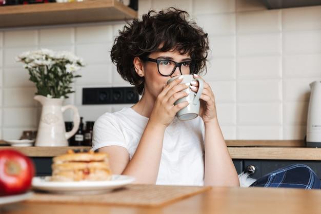 お茶を飲みながらキッチンに座っているかなり巻き毛の女性