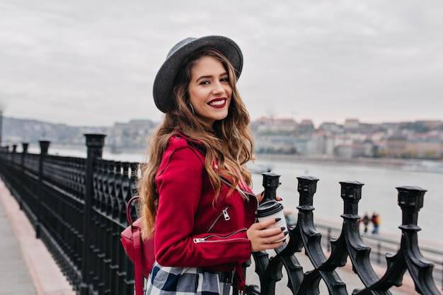 Pretty curly woman with bright makeup enjoying city view from bridge in autumn day