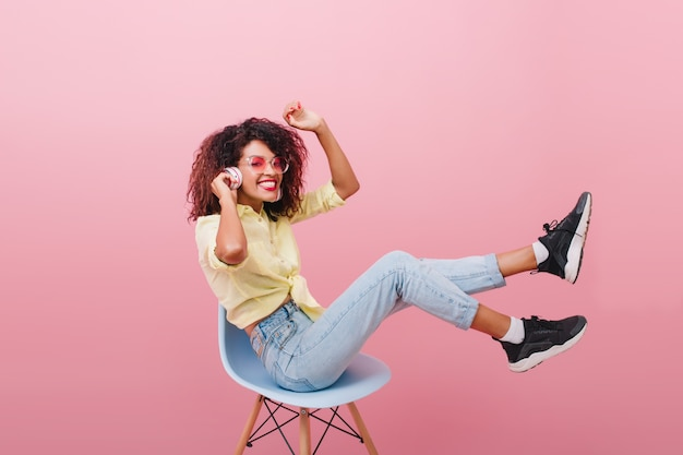 Pretty curly woman with bronze skin posing in new black sneakers. fascinating brown-haired lady in white socks chilling in chair and laughing.