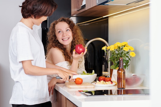Pretty curly young woman drinking apple and looking at girlfriend cutting salad
