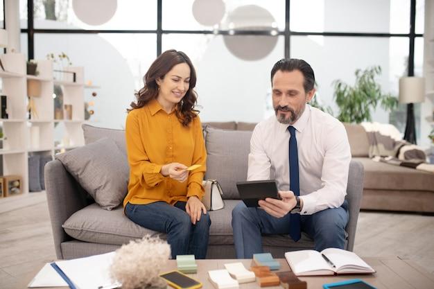 Довольно клиент в желтой рубашке дает кредитную карту менеджеру