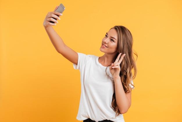 La bella giovane donna abbastanza sveglia fa il selfie dal telefono cellulare