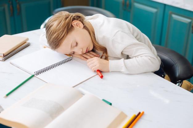 Довольно милая белокурая маленькая девочка спит над своими книгами, сидя за столом и делая домашнее задание