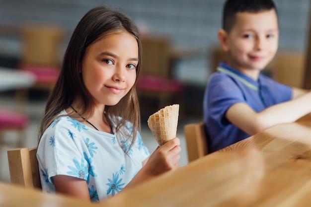 Симпатичная, милая девушка с мороженым отдыхает в кафе со своим братом и очень приятно проводит время.