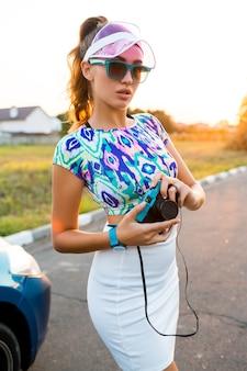 晴れた夏の日のロードトリップ中にポーズをとってレトロなカメラでかわいい女の子。