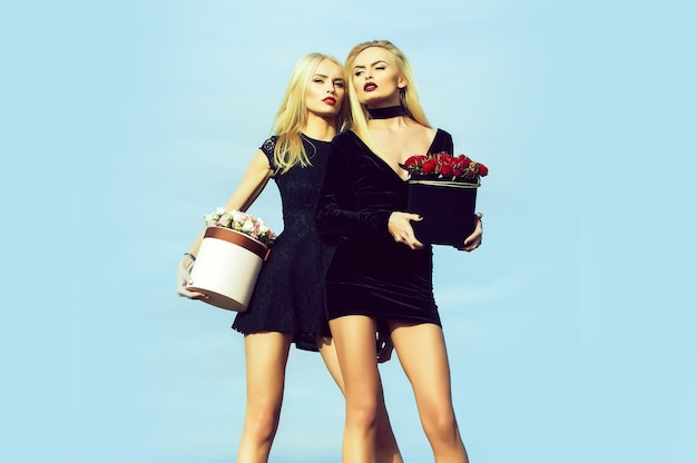 Pretty cute girls or beautiful blond women twins has long legs in sexy dress with rose flowers in box outdoor