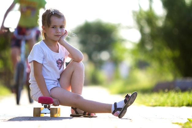 Pretty cute little blond girl in white shorts and t-shirt sitting on pink skateboard