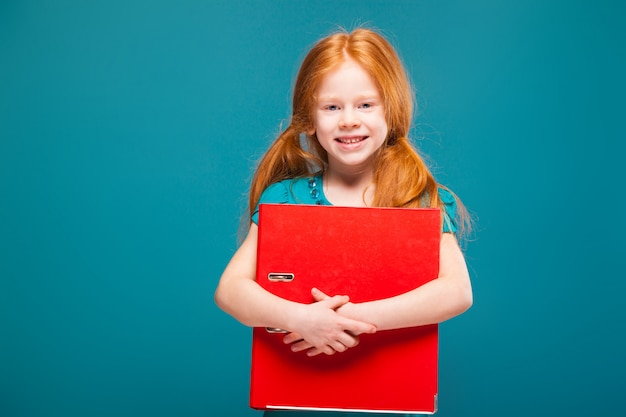 Pretty, cute little girl in blue clothes with long red hair cares papers