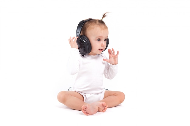 Pretty cute little girl in white pijamas with headphones on head