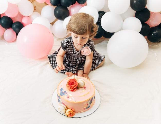 風船とケーキのかわいい女の子。誕生日のコンセプト。上面図