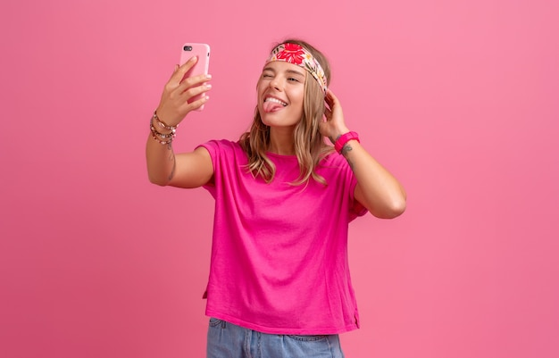 Pretty cute smiling woman in pink shirt boho hippie style accessories smiling emotional fun posing on pink, talking on video chat
