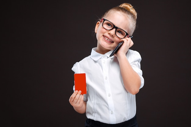 Pretty cute young girl in white shirt and black trousers hold red card and talk on the phone