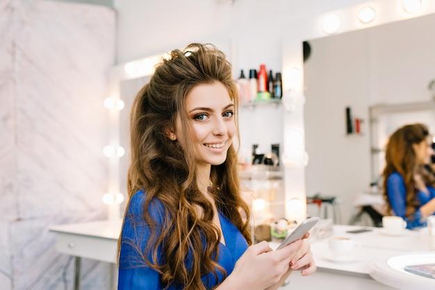 美容院でカメラに笑顔の長いブルネットの髪を持つかなりかわいい若い女性