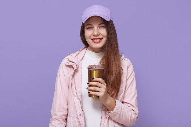 Pretty dark haired european woman has long hair, wears jacket and baseball cap, holds coffee to go in thermo mug, models over lilac wall, looks smiling at camera.