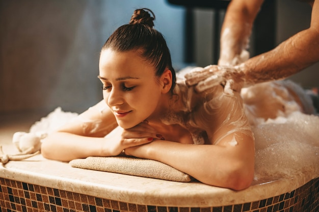 Pretty dark haired female having relaxing massage with foam in a wellness spa turkish hammam.