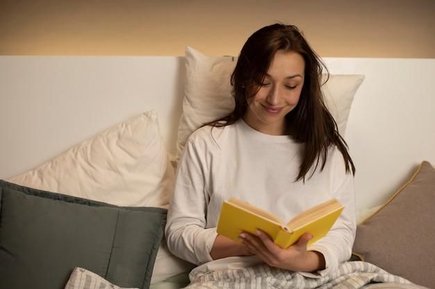 Довольно темноволосая девушка в пижаме читает книгу с желтой обложкой, сидя в кровати
