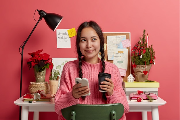 Pretty dark haired girl uses smartphone for surfing social networks, drinks takeaway coffee, looks away, dressed in knitted sweater, poses against desktop with decorated christmas tree