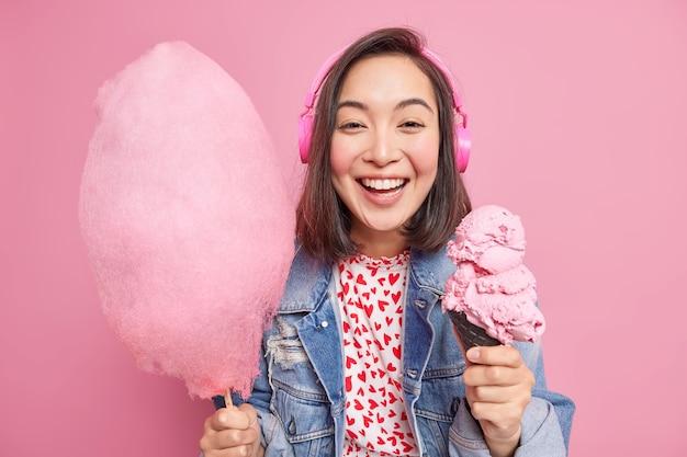 Una giovane donna dai capelli abbastanza scura con espressione positiva tiene gelato congelato e zucchero filato ascolta la traccia audio tramite cuffie vestita con abiti alla moda isolati sul muro rosa