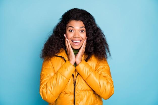 Красивая темнокожая кудрявая дама, держащая руки на скулах, не верит, что скидки низкие цены носить модное желтое осеннее пальто зеленый пуловер изолированный синий цвет стены