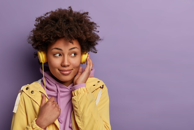 Pretty dark skinned hipster girl listens audio book in headphones, focused aside with dreamy expression, wears casual clothing