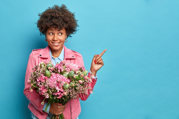 Pretty dark skinned pretty young woman with afro hair indicates aside on copy space holds bouquet gives recommedation isolated over blue studio background.