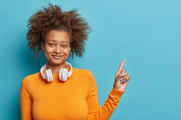 Pretty dark skinned woman with bushy curly hair indicates on copy space demonstrates new item wears casual jumper and stereo headphones around neck.