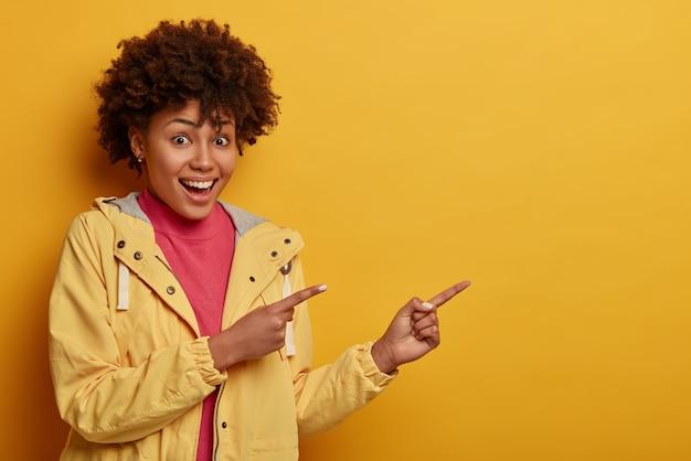 아프로 헤어 스타일을 가진 꽤 어두운 피부의 젊은 여성, 즐겁게 미소 짓고 시원하고 매력적인 것을 광고합니다.