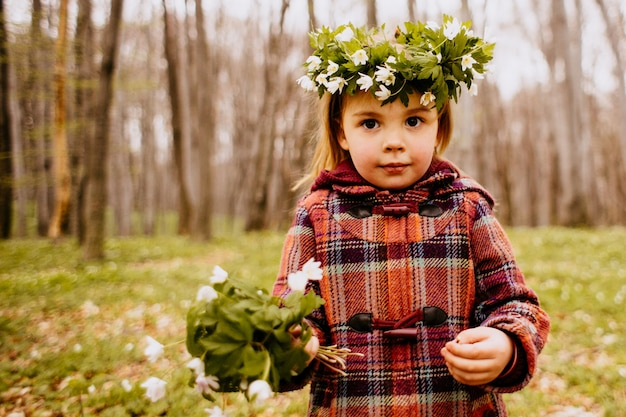 The pretty daughter has a wreath and bouquet  of snowdrops