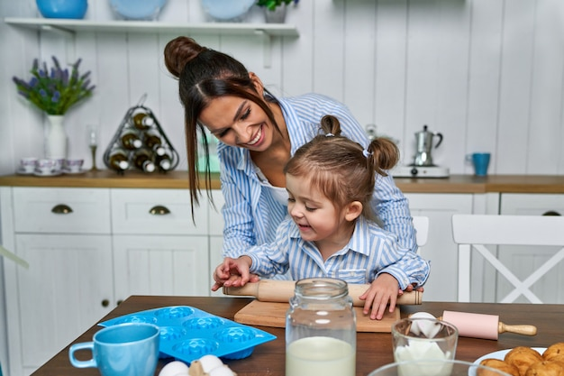 Pretty daughter and her young mom roll out the dough in the kitchen on the table.