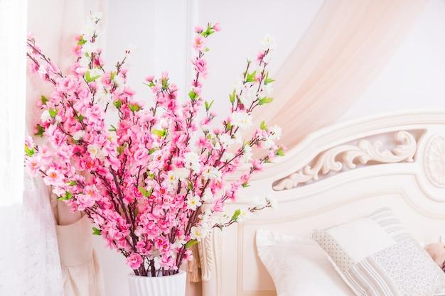 Красивое украшение из свежих розовых весенних цветов в высокой вазе рядом с кроватью Premium Фотографии