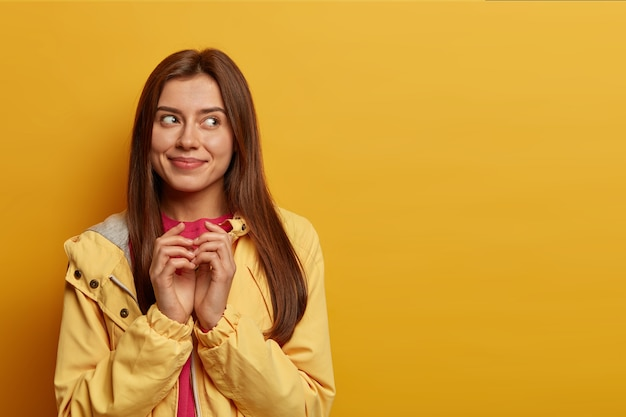 Pretty delighted woman schemes something, steepls fingers and looks with intention aside, has cunning look, made up good idea, smiles pleasantly, wears windbreaker, isolated on yellow  wall