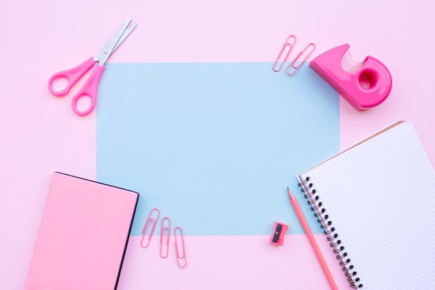 Pretty desktop composition with notebook, scissors, and books on pink background with blu