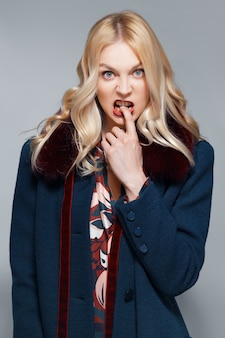 かなりがっかりした少女の指を噛む、不確実な気分。毛皮の襟付きのコートの女性の肖像画。