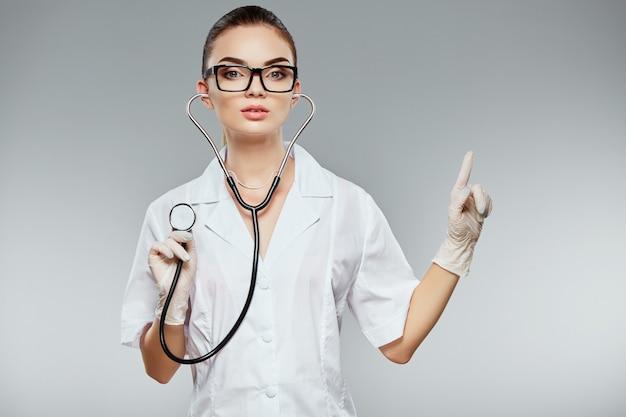 Симпатичный доктор с каштановыми волосами и обнаженным макияжем носит белую медицинскую форму, очки, стетоскопы и белые перчатки на сером фоне студии, портрет, указывая пальцем.