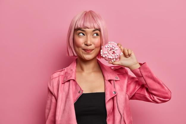 Симпатичная мечтательная дама с волосами цвета боб, держит в руках аппетитный пончик, испытывает искушение съесть калорийный десерт, носит стильный розовый пиджак.