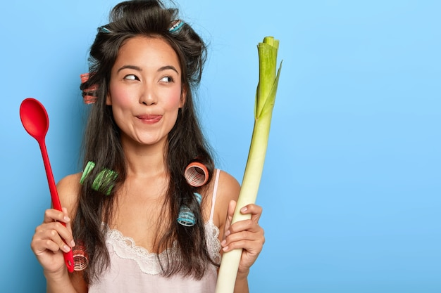 Pretty dreamy woman licks lips, holds spoon and fresh vegetable, looks aside, ready for preparing delicious nutritious dish, models indoor