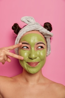 Pretty dreamy young female model makes peace gesture over eye, applies nourishing green mask on face, wears headband, stands naked indoor, enjoys beauty treatments, isolated on pink  wall