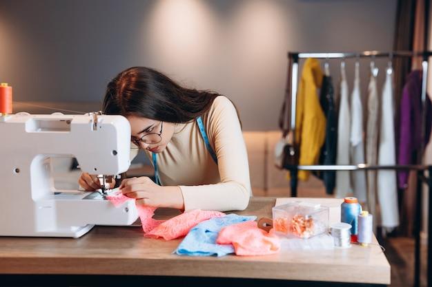 안경에 예쁜 양장점 여자 재봉틀에 옷을 바느질