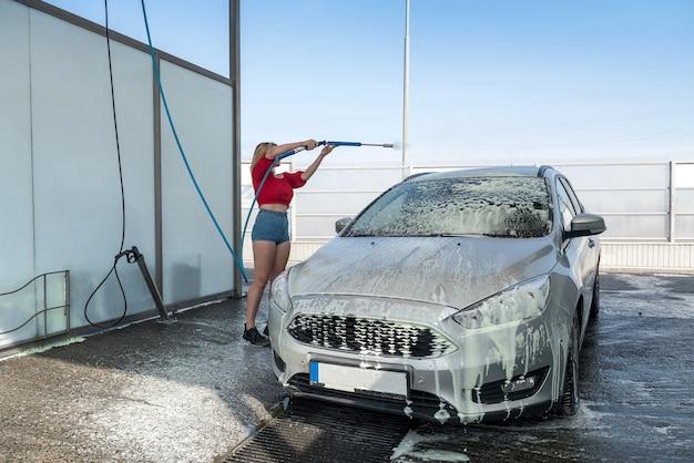 고압 호스를 사용하여 그녀의 차를 먼지에서 청소하는 예쁜 드라이버 여자가 차에 클리너를 적용합니다.