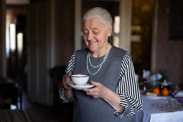 Довольно пожилая женщина с чашкой в руках. бабушка с улыбкой на лице пьет кофе.