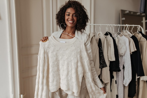 Pretty elegant dark-skinned woman in beige jacket smiles, looks at front and holds hanger with white knitted sweater